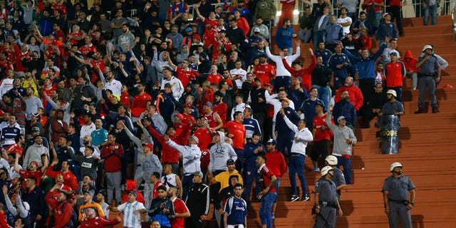 Police stand next to fans of Argentina's Independiente at the end of a Copa Libertadores soccer match against Brazil's Santos