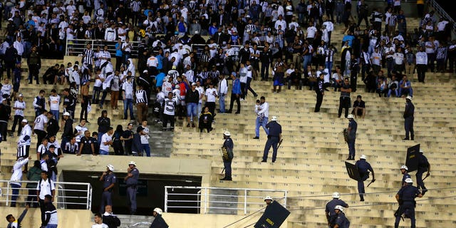 Police order the fans of Brazil's Santos to leave the grandstand after fights broke out in the stands at the end of a Copa Libertadores soccer match