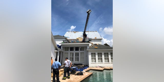 This photo released by the Orlando Fire Department shows firefighters surveying the scene where a crane tipped over, damaging a house in Orlando, Fla., on Tuesday.