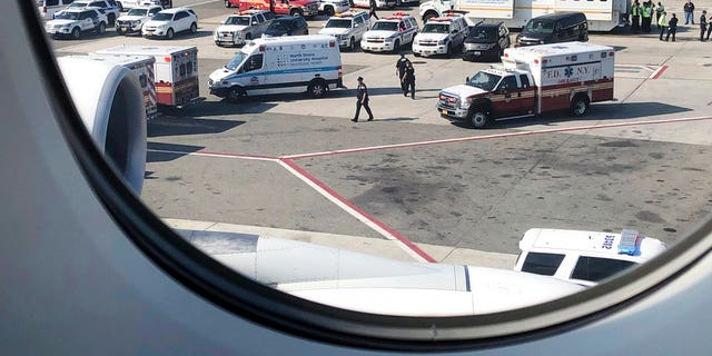 Emergency response crews gather outside a plane at New York's Kennedy Airport amid reports of ill passengers aboard a flight from Dubai on Wednesday.