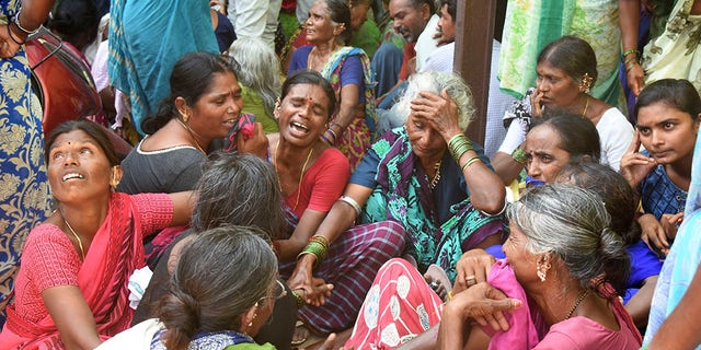Relatives of victims of a bus accident wail near a hospital in Jagtiyal district of Telangana, India.