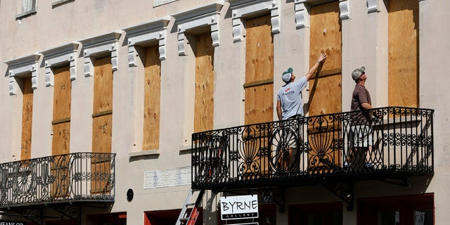 Derek Mundy, left, and Kris Crouse boards up the Confederate House in preparation for Hurricane Florence in downtown Charleston, S.C.
