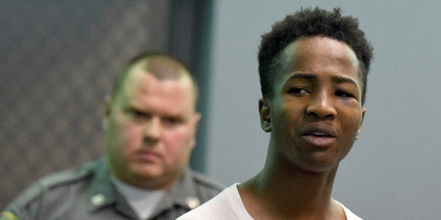 Shyhiem Adams mouths something to his mother and aunt sitting in the courtroom gallery during arraignment in Enfield Superior Court on charges in the stabbing death of 16-year-old of Justin Brady.