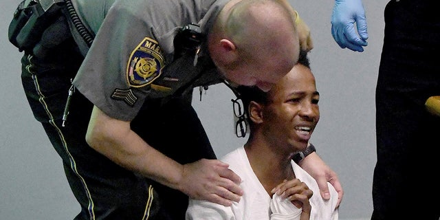 Shyhiem Adams is aided by a court marshal after collapsing as friends of the Justin Brady were screaming at Adams during his arraignment in Enfield Superior Court on charges in the stabbing death of 16-year-old of Justin Brady.