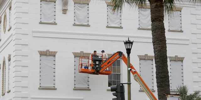 Workers cover the windows of the historic Charleston County Courthouse in Charleston, S.C., in preparation for the advancing Hurricane Florence.