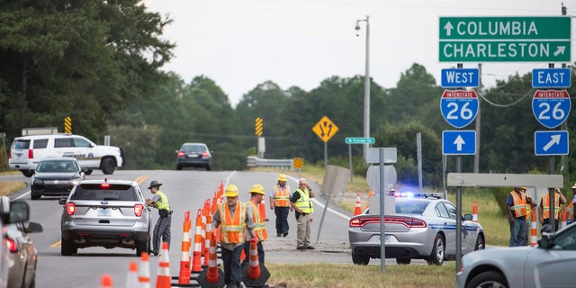 South Carolina state troopers work with D.O.T. employees at an access ramp to I-26 in Columbia, South Carolina.