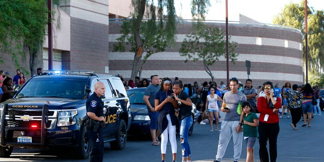 In this Sept. 11, 2018 photo, students and parents wait outside Canyon Springs High School in North Las Vegas after a fatal shooting near a baseball field.
