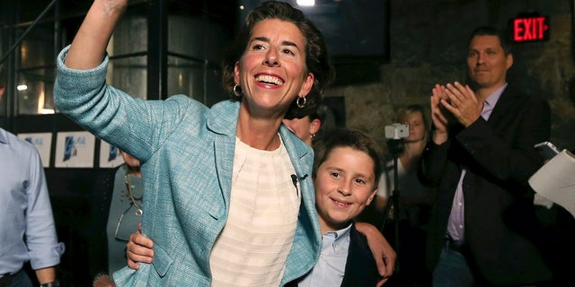 FILE: Incumbent Democratic Rhode Island Gov. Gina Raimondo waves to supporters alongside her son, Thompson, at her primary night victory party.