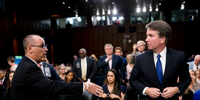FILE PHOTO: The father of a student who was killed in the Stoneman Douglas High School shooting in Parkland, Fla., left, attempted to shake hands with Supreme Court nominee, Brett Kavanaugh, right, as he leaves for a lunch break while appearing before the Senate Judiciary Committee on Capitol Hill in Washington.