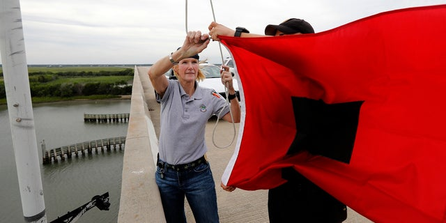 Isle of Palms Fire Chief Ann Graham, at left, and Isle of Palms police officer Thomas Molino III raise a tropical storm warning flag over the Isle of Palms Connector shortly after Charleston County, S.C., went under a tropical storm warning due to Hurricane Florence.