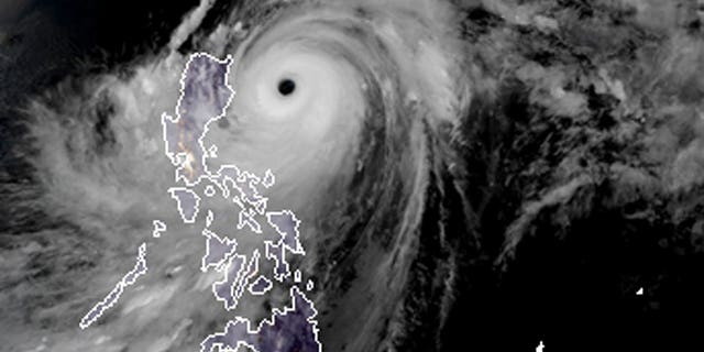 a satellite image with land graphic borders shows the width and trajectory of Typhoon Mangkhut as it approaches the Philippines.