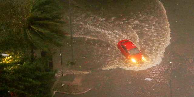 A vehicle swerves through a flooded street in Manila after Typhoon Mangkhut wreaked havoc in the area.