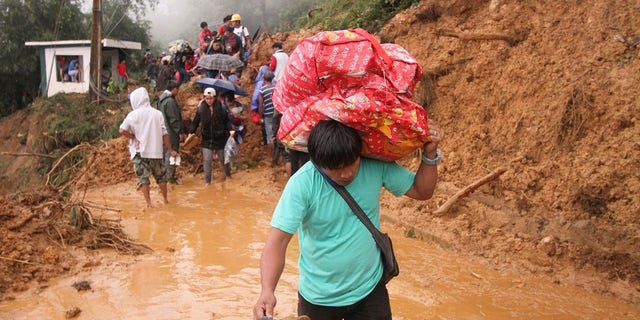 Families and relatives of miners in Itogon township, Benguet province in the northern Philippines, carry their belongings as they evacuate following landslides which were triggered by Typhoon Mangkhut.