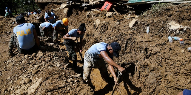 Rescuers push water along a drainage as operations continue at the site where victims are believed to have been buried by a landslide after Typhoon Mangkhut lashed Itogon, Benguet province.