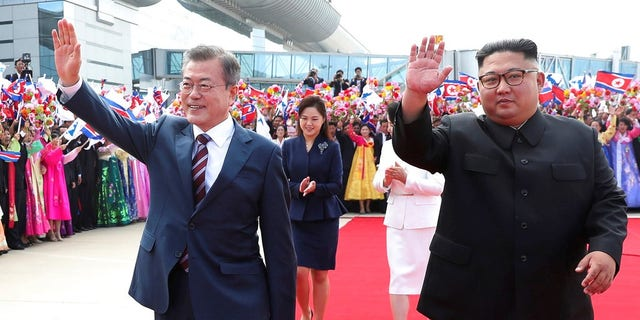 South Korean President Moon Jae-in, left, waves while walking with North Korean leader Kim Jong Un during a welcome ceremony at Sunan International Airport in Pyongyang, North Korea.