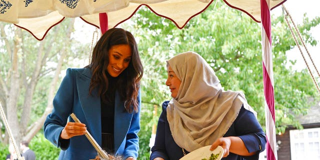 """Meghan, the Duchess of Sussex, left, reacts with one of the women behind the cookbook """"Together"""" during a reception at Kensington Palace."""