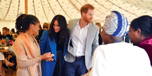 "Meghan, the Duchess of Sussex, talks to her mother Doria Ragland, with Prince Harry by her side as they attend a reception for the cookbook ""Together."""