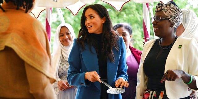 "Meghan, the Duchess of Sussex, centre, reacts with one of the women behind the cookbook ""Together"" during a reception at Kensington Palace."