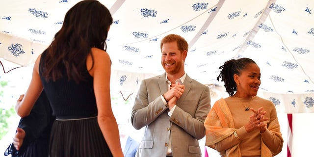 """Britain's Prince Harry and Doria Ragland, gesture as Meghan, the Duchess of Sussex, left, hugs a woman involved with the cookbook """"Together"""" during a reception at Kensington Palace."""
