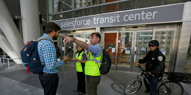 FILE: Mike Eshleman, with AC Transit, directs people away from the Salesforce Transit Center after its closure.