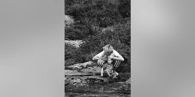 Princess Diana plays with Prince Harry near a stream.