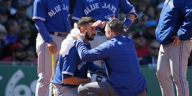 Toronto Blue Jays' Chris Colabello, center left, is tended to after being hit by a pitch in the fourth inning of a baseball game against the Boston Red Sox at Fenway Park, Sunday, April 17, 2016, in Boston. (AP Photo/Steven Senne)