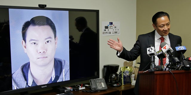 San Francisco Public Defender Jeff Adachi gestures while standing beside a picture of police officer Jason Lai, who resigned earlier in April.