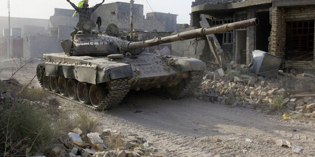 Iraqi security forces advance their positions during heavy fighting against Islamic State group militants in Fallujah on Tuesday.