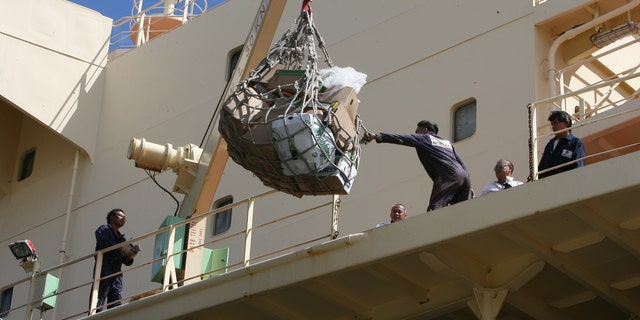 Crew members pull supplies onto the deck of the Newlead Castellano