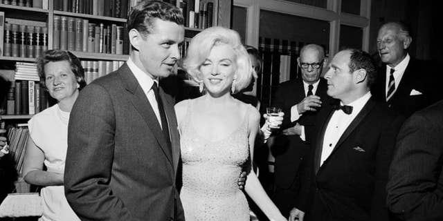 Marilyn Monroe is seen wearing the iconic gown from President Kennedy's birthday fundraiser during a reception in New York City. Standing next to Monroe is Steve Smith, President Kennedy's brother-in-law. This photo is provided by the John F. Kennedy Presidential Library and Museum.
