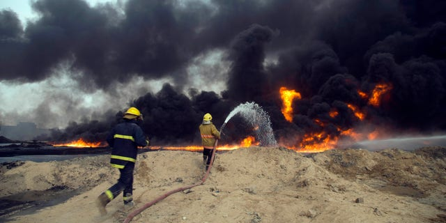 Iraqi firefighters battle large fire at oil wells as they trying to prevent the flames from reaching the residential neighborhoods in Qayyarah.