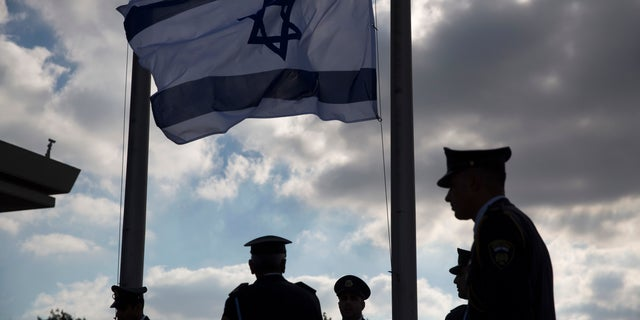Members of the Knesset guard stand next to the Israeli flag at half-staff in preparations to display the coffin of former Israeli President Shimon Peres at the Knesset, Israel's Parliament, in Jerusalem, Wednesday, Sept. 28, 2016.
