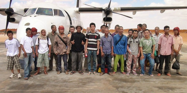 Sailors standing for a group photograph as they prepare to board an airplane after a Somali pirate said they were released.
