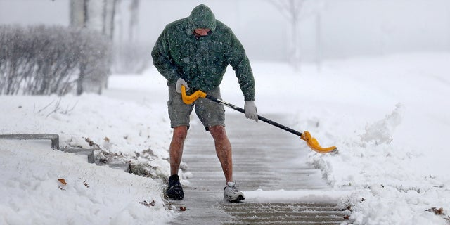 Peter Lidstone shovels his sidewalk in St. Cloud, Minn.