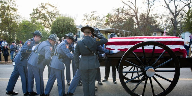 An honor guard loads the casket of Americus police officer Nicholas Smarr onto a caisson after the funeral.