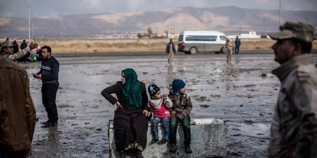 An Iraqi woman displaced from Mosul and her 2 children sit on top of an old refrigerator at a gathering point for displaced people, in Bartella, around 19 miles from Mosul.