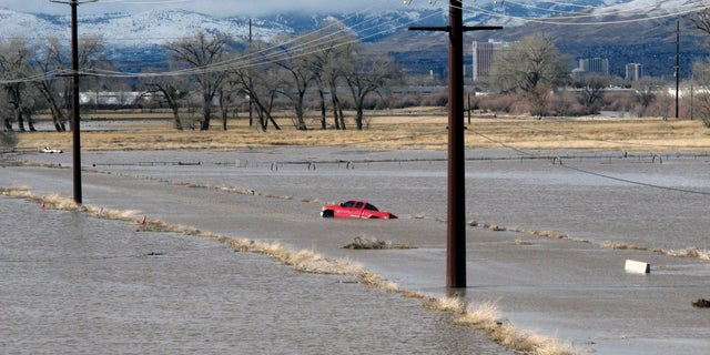 A red pickup truck sits abandoned it after it got stuck in floodwaters at a University of Nevada, Reno, research farm bordering the Truckee River.