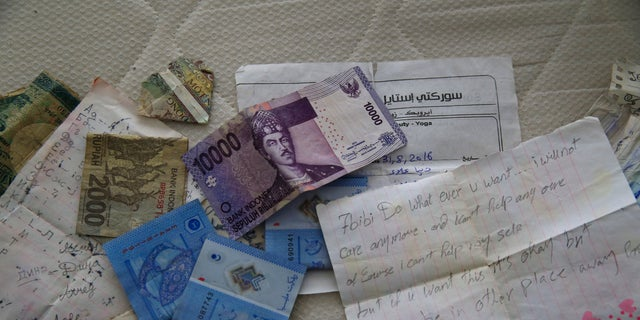 Banknotes of different currencies on a bed inside the home where the suspect was hiding.