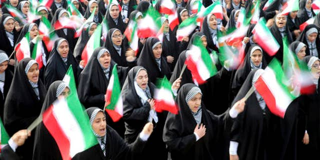 Iranian school girls wave national flags during the annual rally in Tehran.