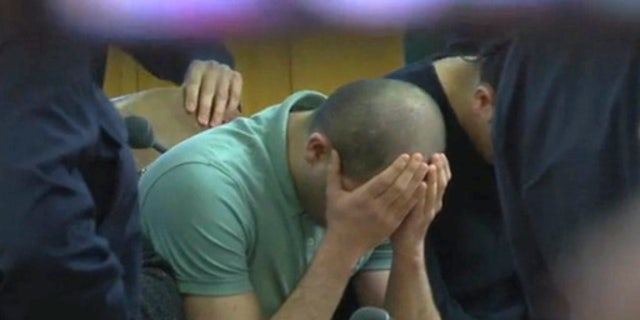 A defendant covers his face at the beginning of the trial.