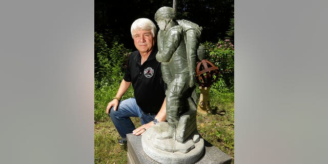 Former Army medic James McCloughan kneels next to a statue presented to him by a fellow soldier in South Haven, Michigan, in February.