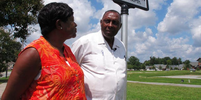 "In this Aug. 16, 2017 photo, the Rev. Nelson Johnson and his wife, Joyce, stand beside a historical marker for the ""Greensboro Massacre"" in Greensboro, N.C. Near that spot on Nov. 3, 1979, Nazis and members of the Ku Klux Klan attacked marching workers, leaving five dead and Johnson injured."