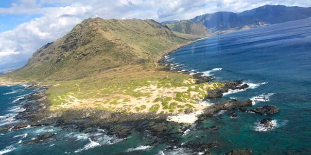 In this Friday, Aug. 18, 2017, photo provided by the U.S. Coast Guard, an MH-65 helicopter crew from Coast Guard Air Station Barbers Point passes Ka'ena Point in Hawaii.