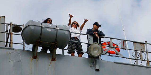 Jennifer Appel, center, raises her arms from the USS Ashland at White Beach Naval Facility in Okinawa, Japan. At left is Tasha Fuiava, and at right the Ashland's Command Master Chief Gary Wise.