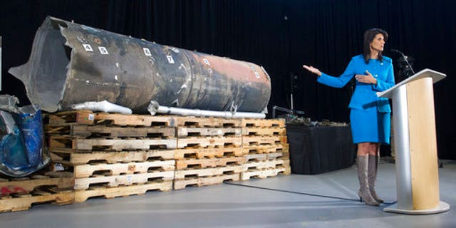 Haley gestures as she speaks in front of recovered segments of an Iranian missile.