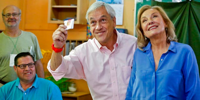 Pinera, with his wife, Cecilia Morel, showing his vote during the runoff.