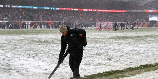 A worker clears snow from field lines at Soldier Field during an NFL game between the Chicago Bears and Cleveland Browns in Chicago on Sunday.