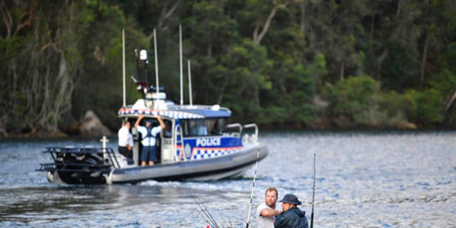 Fishermen guide their boat past a police vessel at the scene where a seaplane crashed into the Hawkesbury River.