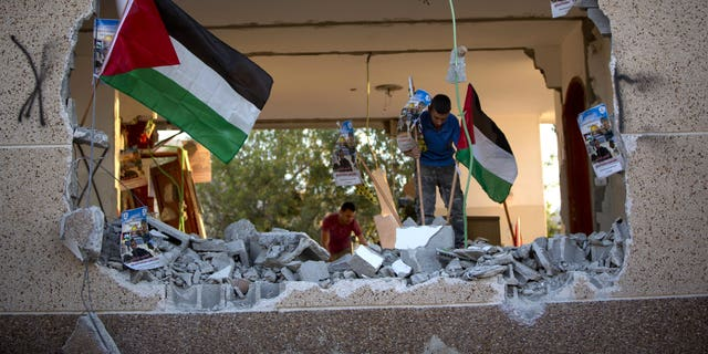 Palestinians place national flags and party banners in what was left of Bashar Masalha's house.