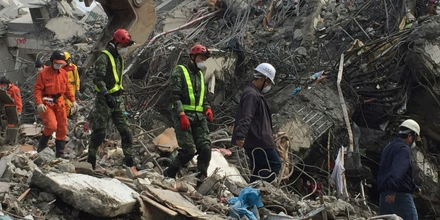 Rescue teams digging through the rubble of collapsed buildings Thursday.